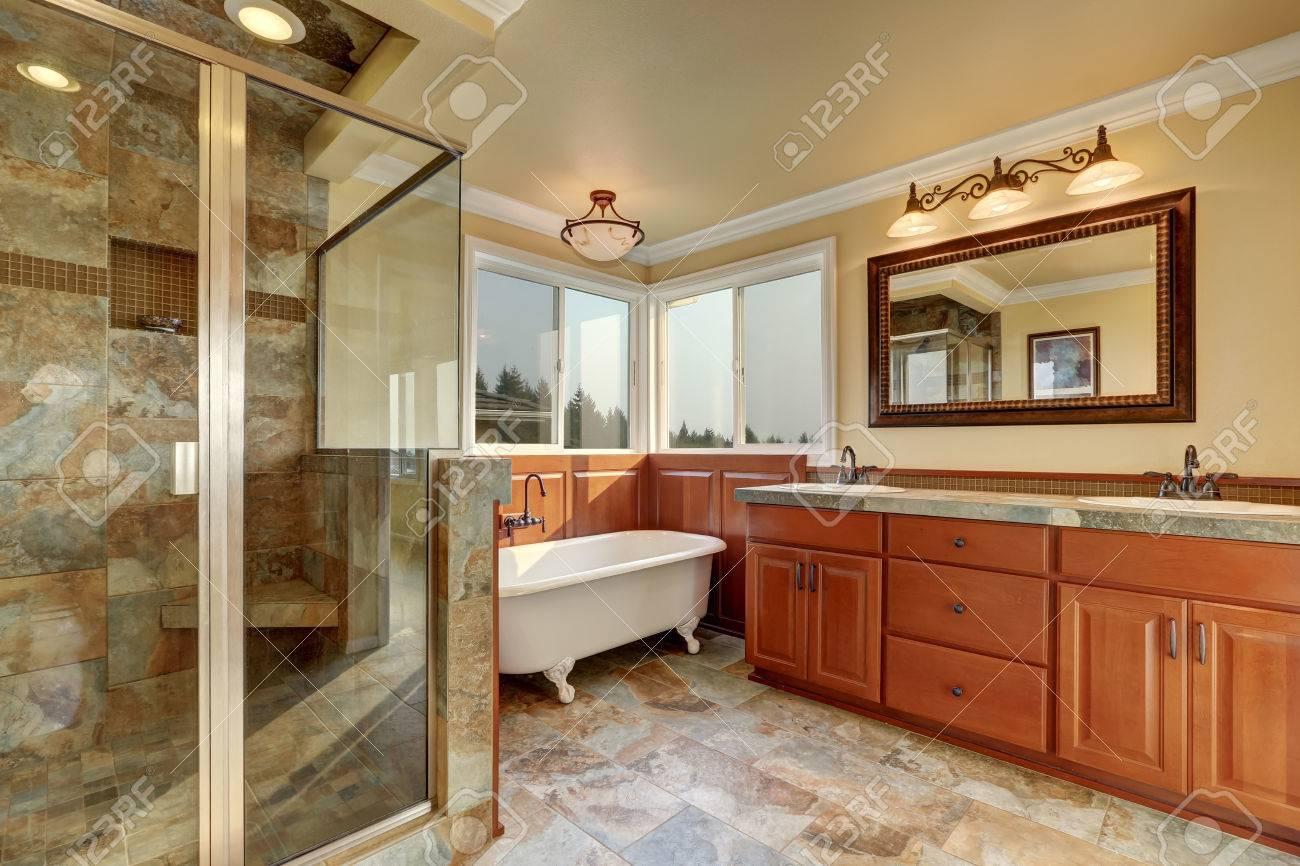 Salle de bains avec carreaux de faïence beige et douche en verre. Cabinet  en bois avec navire coule et miroir. Northwest, États-Unis