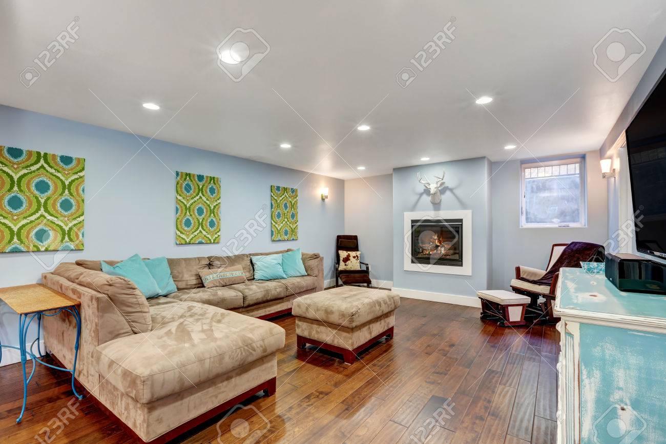 Murs bleu pastel en inter-sol du salon. Grand canapé d\'angle avec des  oreillers bleu et pouf. Northwest, États-Unis