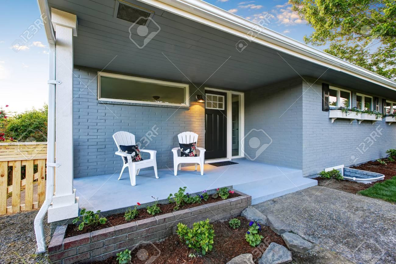 Esterno Casa Di Campagna esterno della casa blu della campagna con il piccolo portico del pavimento  di calcestruzzo con le sedie. northwest, stati uniti