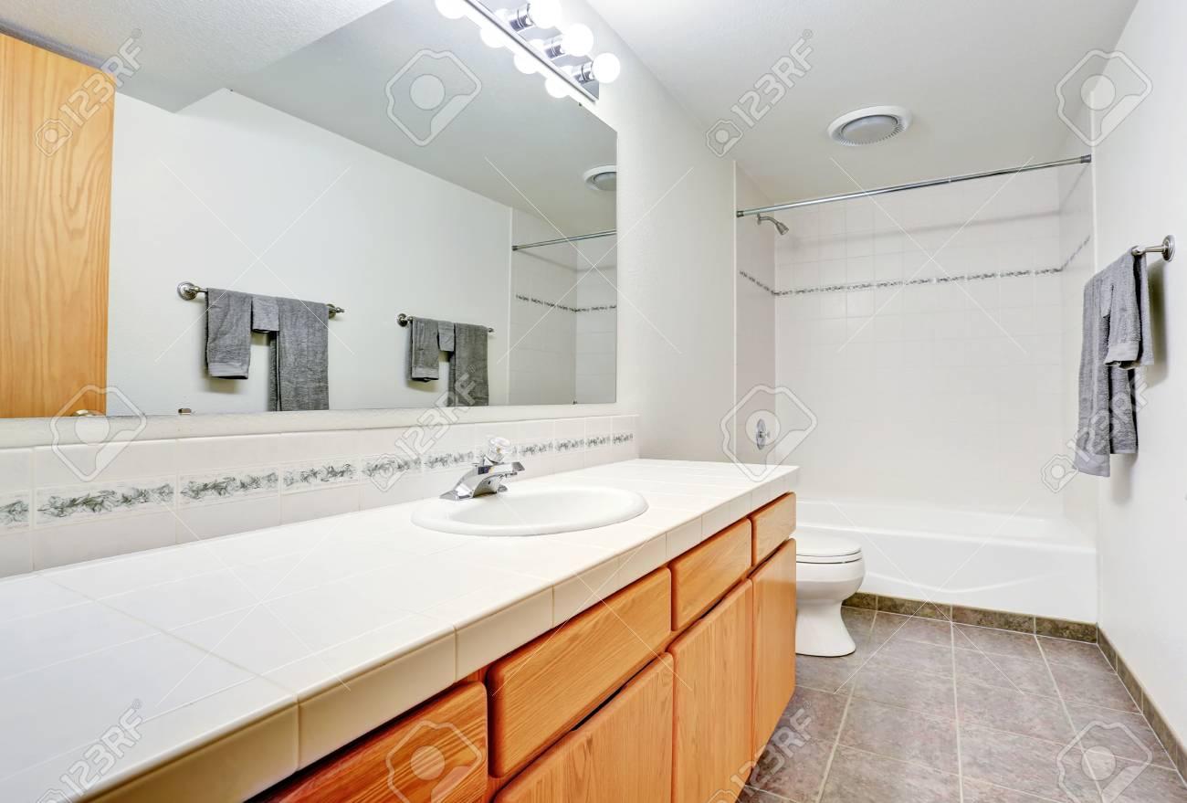 Au Comptoir Du Carrelage grand meuble-lavabo avec comptoir de carrelage dans la salle de bain  blanche. nord-ouest des États-unis