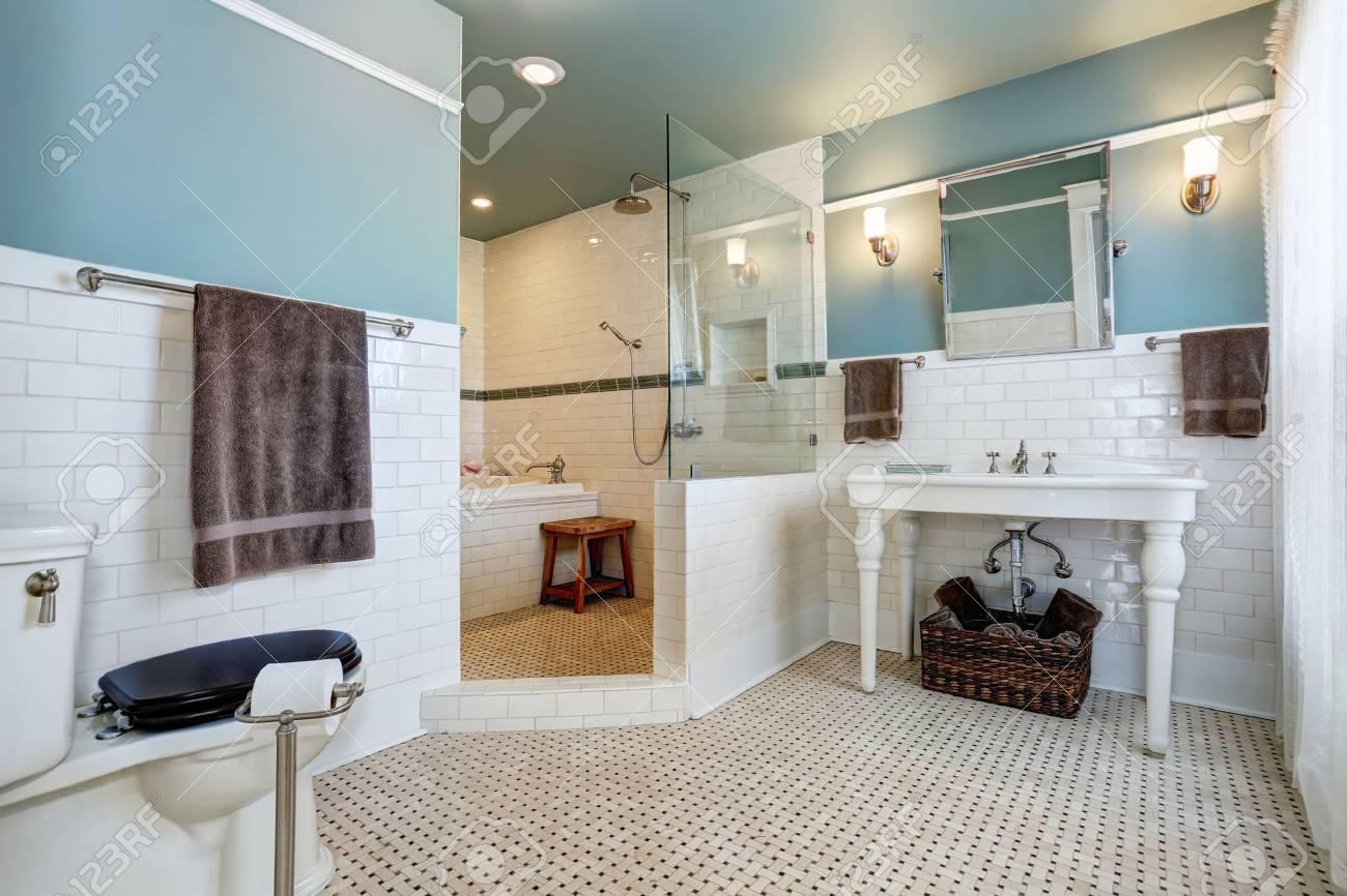 Intérieur de la salle de bain bleu avec mur de carreaux blancs, évier blanc  et baignoire. Northwest, États-Unis