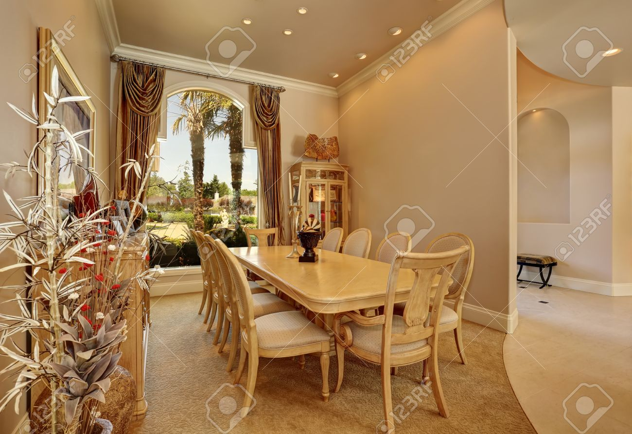 Luxury Beige Dining Room Interior With Large Arch Window, Golden Curtains,  Vintage Wooden Table
