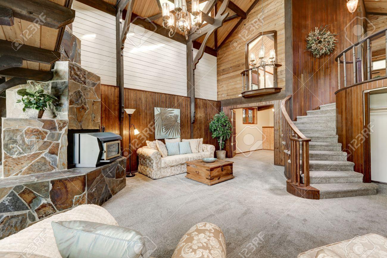 Intérieur chalet en bois moderne avec salle de séjour de près. cheminée  magnifique avec garniture de carrelage en pierre naturelle et un escalier  ...