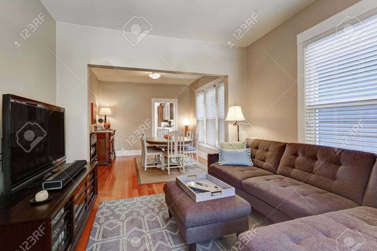 Intérieur du salon américain avec canapé d\'angle marron, pouf et téléviseur  noir. Vue de la table à manger à l\'arrière-plan. Nord-ouest, États-Unis