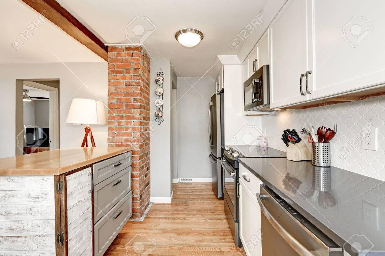 Intérieur de la cuisine blanche avec des détails gris. Backsplash blanc,  comptoirs brillants, îlot de cuisine conçu dans le style ancien et mur ...