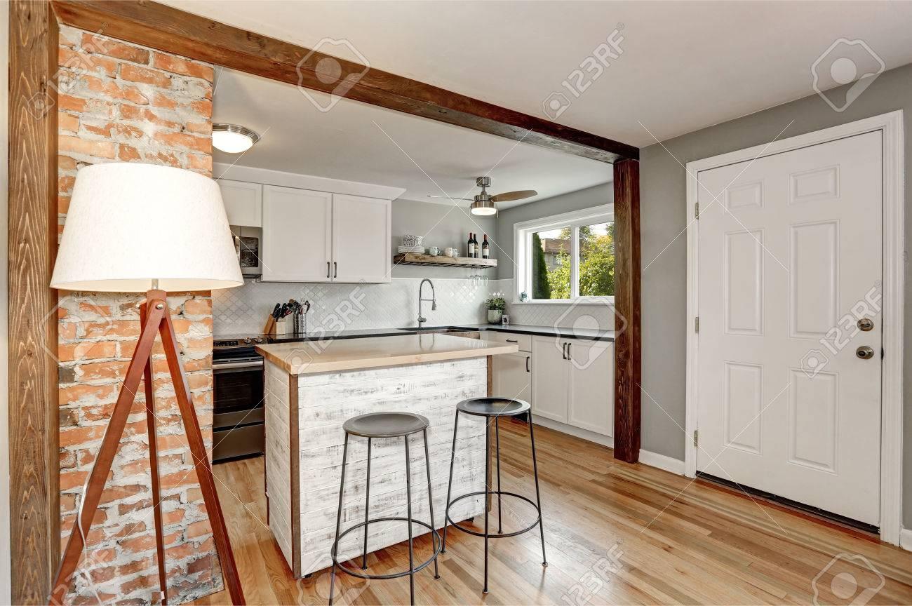 Intérieur blanc de cuisine avec détails gris. Le dosseret blanc et la  petite île de cuisine conçues dans un ancien style et un mur d\'accent de ...