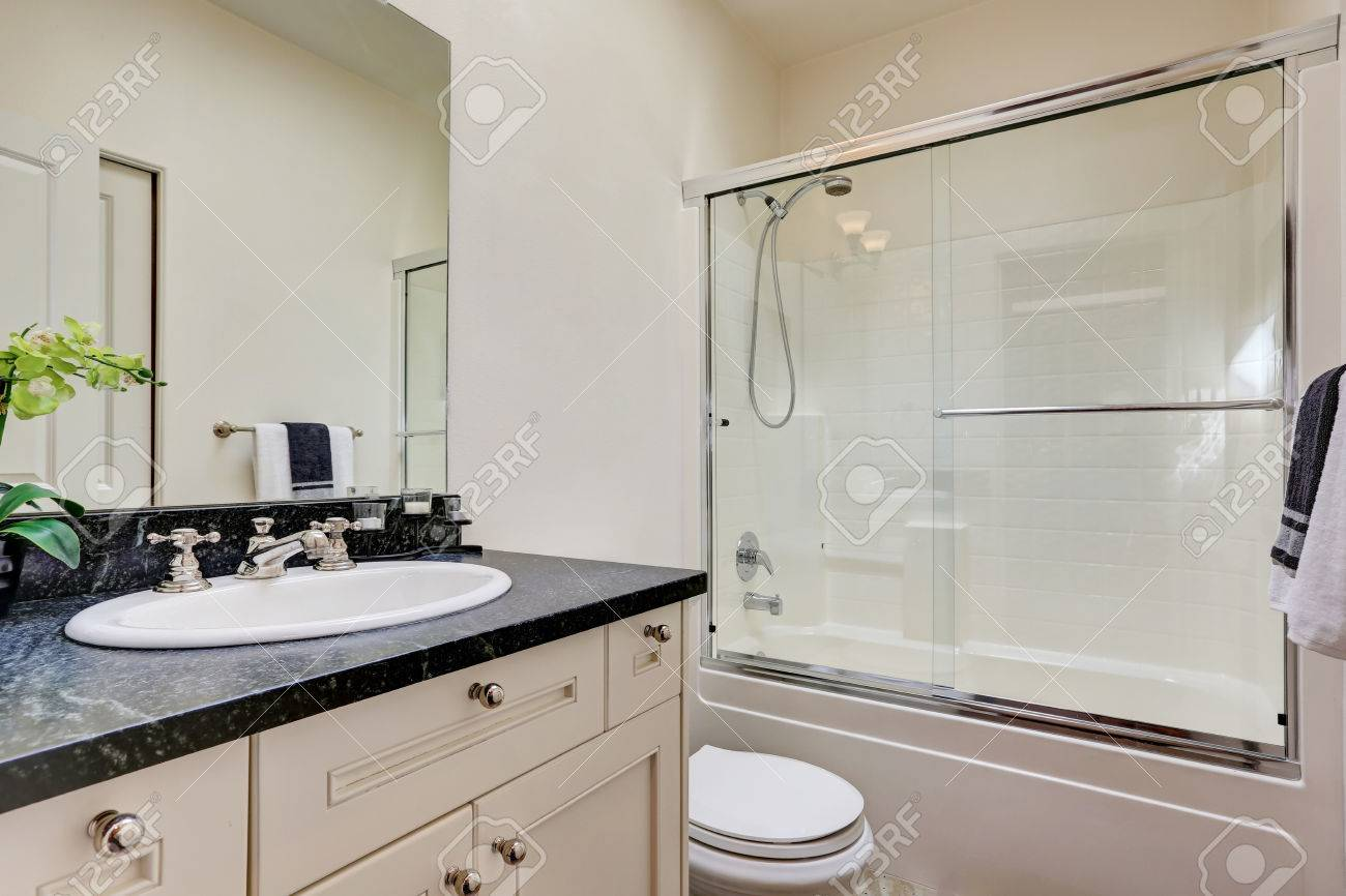 White Bathroom Interior With Glass Shower And Vanity With Black ...