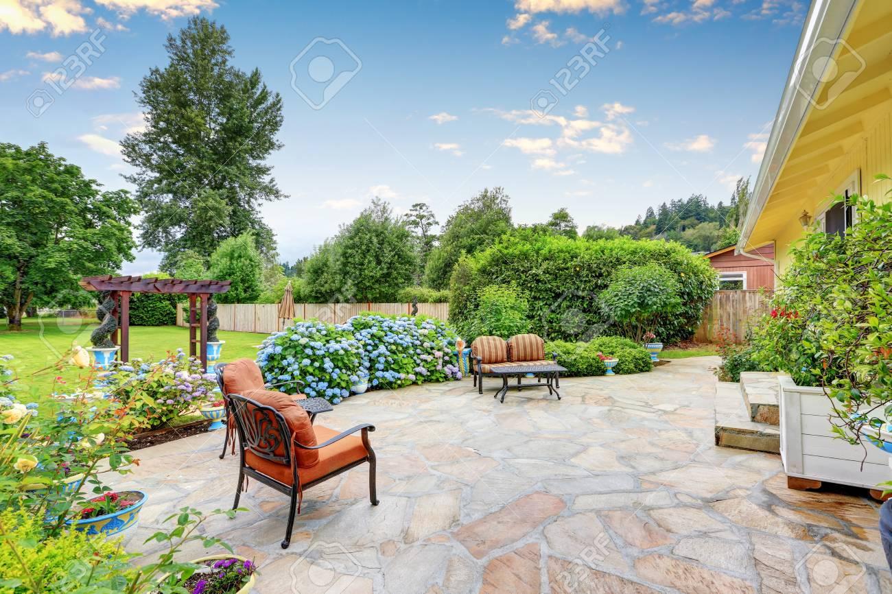 Terrasse bien conçu avec un sol en pierre dans la cour arrière d\'une maison  jaune. Espace détente avec mobilier de jardin confortable et la floraison  ...