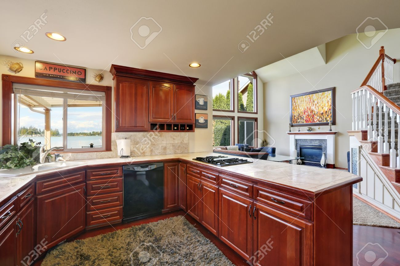 Mahogany Kitchen Cabinets, Marble Counter Tops, Backsplash And Gray Fluffy  Carpet On The Floor