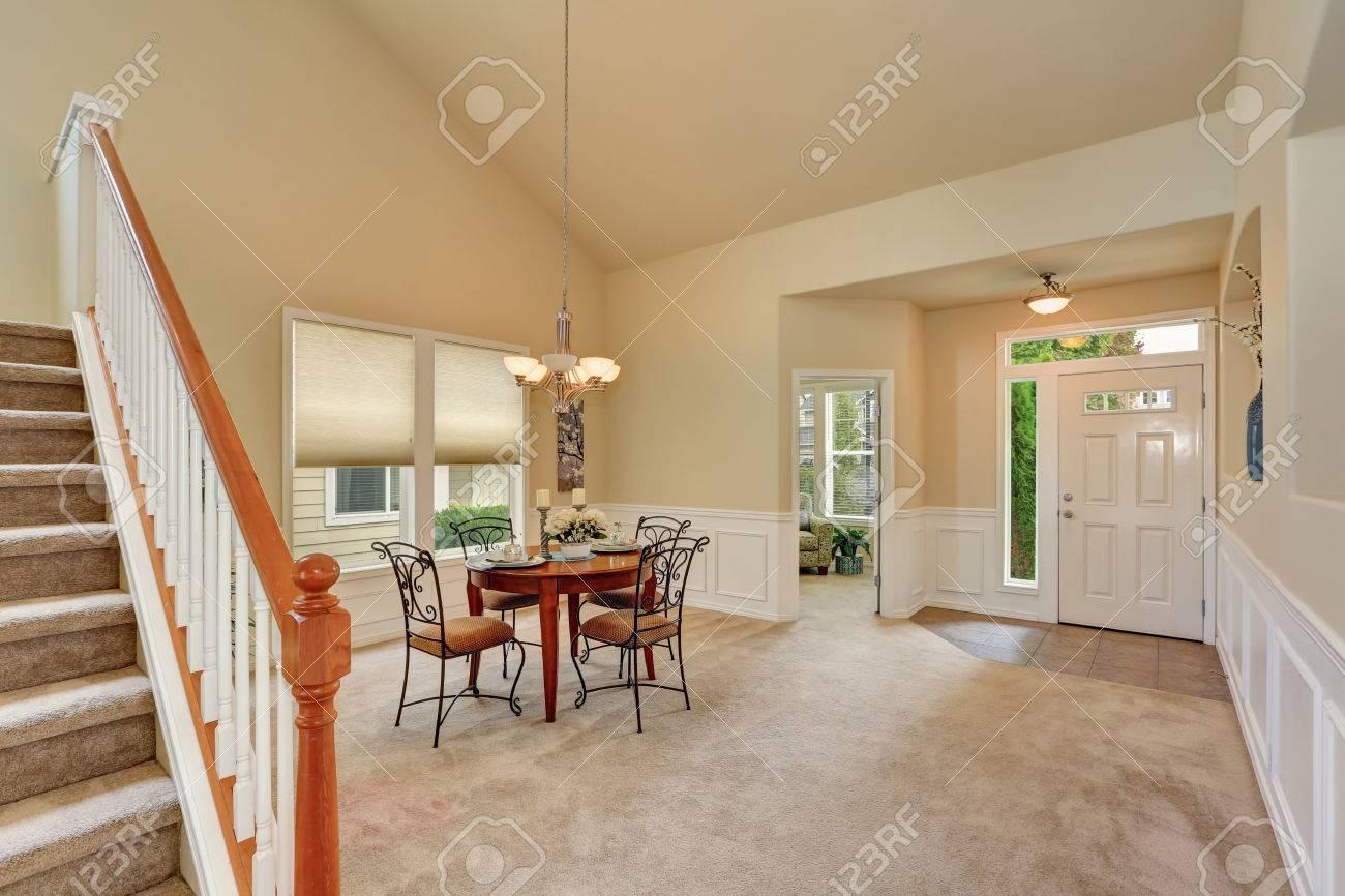 Salle à manger beige intérieur avec de hauts plafonds et les escaliers.  table élégante et des chaises en fer forgé. Nord-Ouest, États-Unis