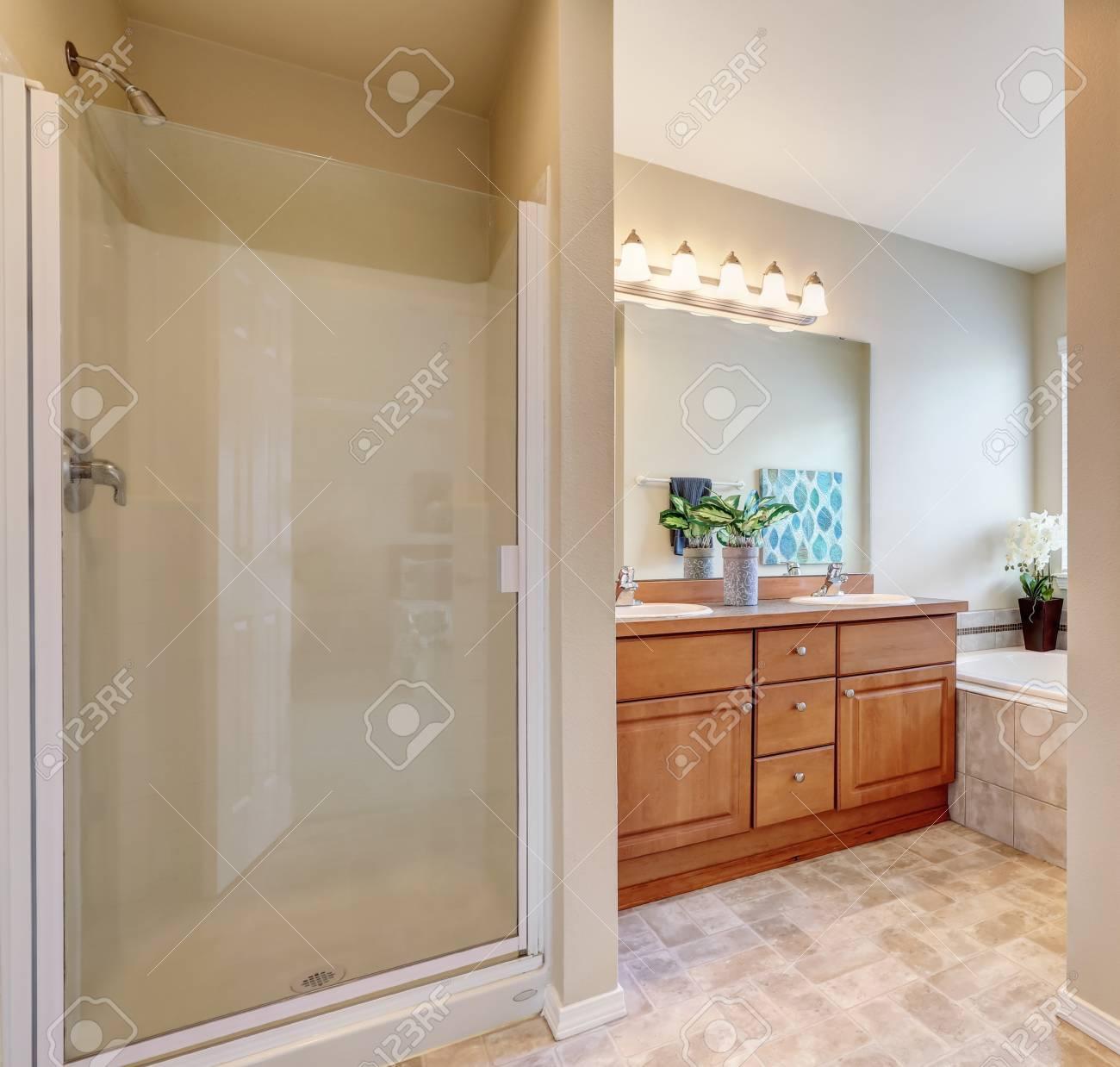 Petit Meuble Vasque Salle De Bain intérieur de la salle de bain avec porte vitrée, vue sur la baignoire et  petit meuble lavabo double vasque avec miroir. nord-ouest des États-unis