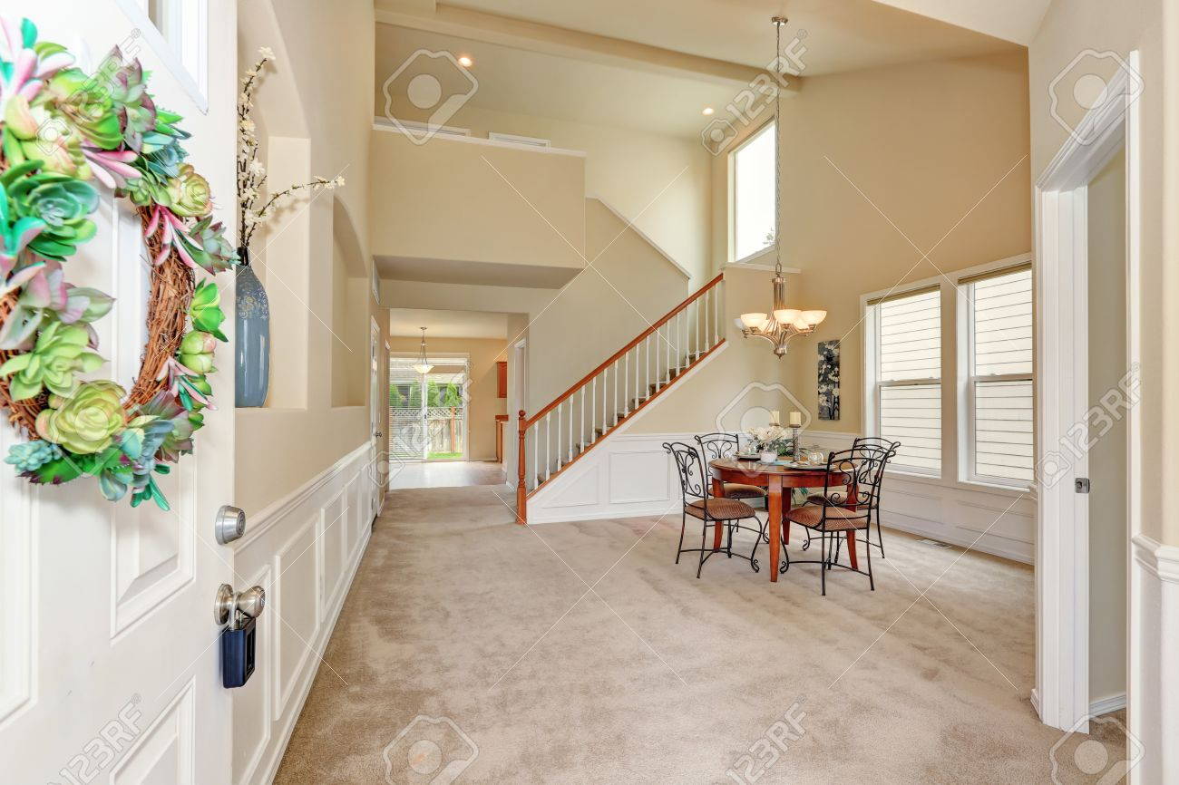 Opened Front Door To High Ceiling Beige Dining Room Interior With Carpet Floor And Staircase