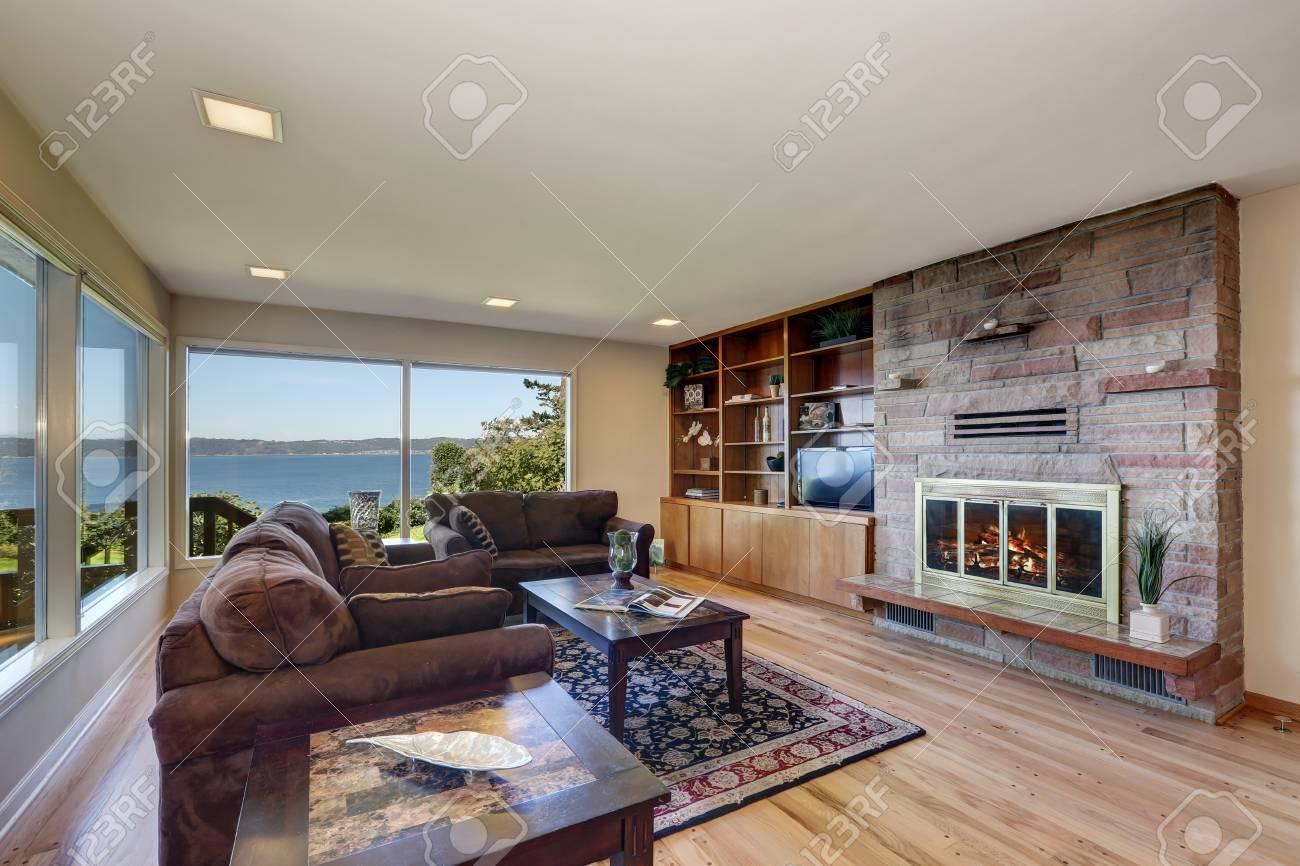 Intérieur de salon joliment meublé avec de grandes fenêtres donnant sur la  vue sur l\'eau. Dispose de parquet, de canapés en chocolat marron, d\'un ...