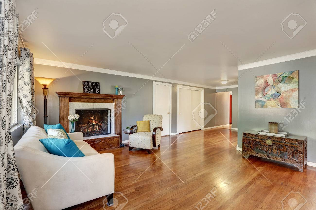 Living Room Interior With Polished Hardwood Floor Gray Walls Fireplace Wooden Carved Trim