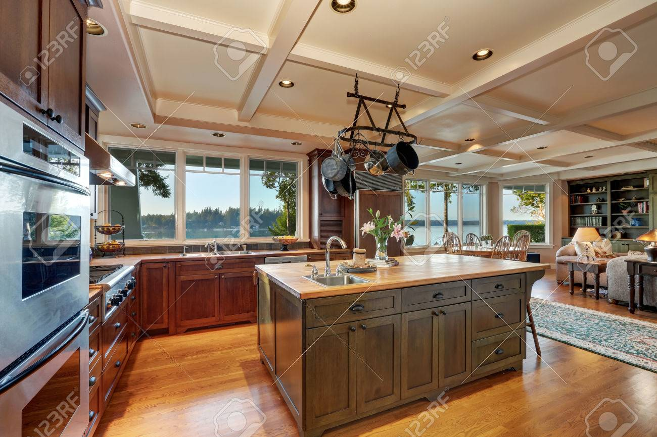 Large kitchen island with hanging pot rack above in open plan..