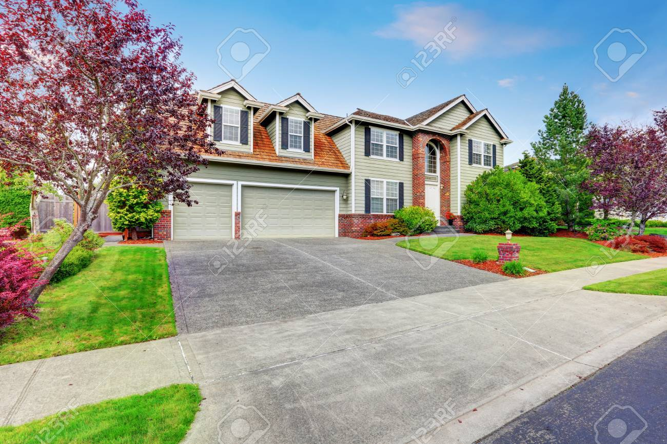 luxury house exterior with red brick trim and arched entry double doors garage with concrete