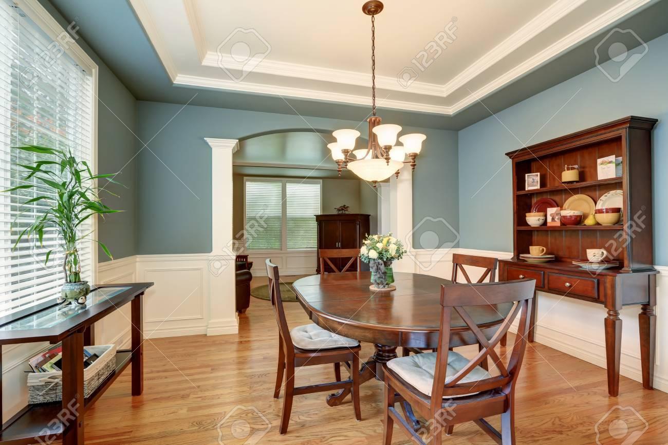 Interior clásico comedor americana con paredes verdes, armario de madera,  piso de madera de la vendimia. Decorado con rosas frescas en un florero. ...