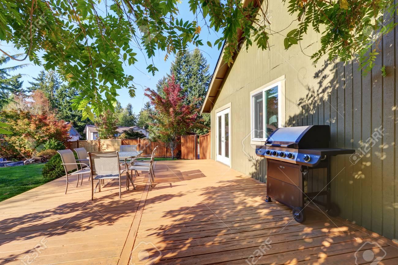 Cour arrière avec terrasse en bois, mobilier de jardin et barbecue.  Nord-ouest des États-Unis