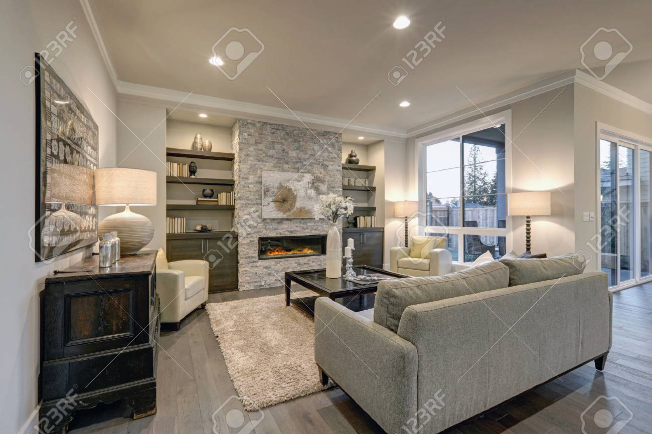 El Interior De La Sala De Estar En Colores Gris Y Marrón Presenta Un Sofá Gris Encima De Los Pisos De Madera Oscura Que Dan A La Chimenea De Piedra