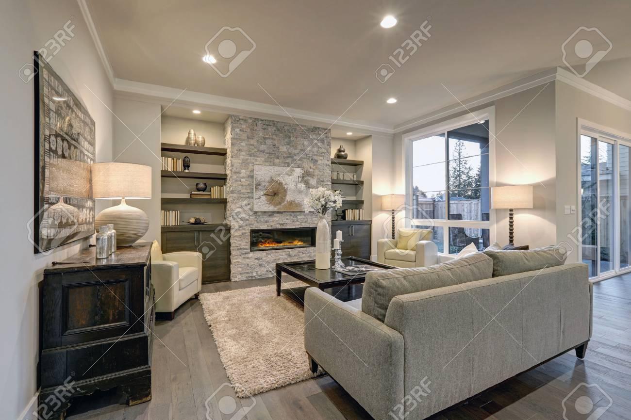 Soggiorno Con Divano Grigio Scuro l'interno del soggiorno nei colori grigio e marrone è caratterizzato da un  divano grigio in cima a pavimenti in legno scuro e un camino in pietra con