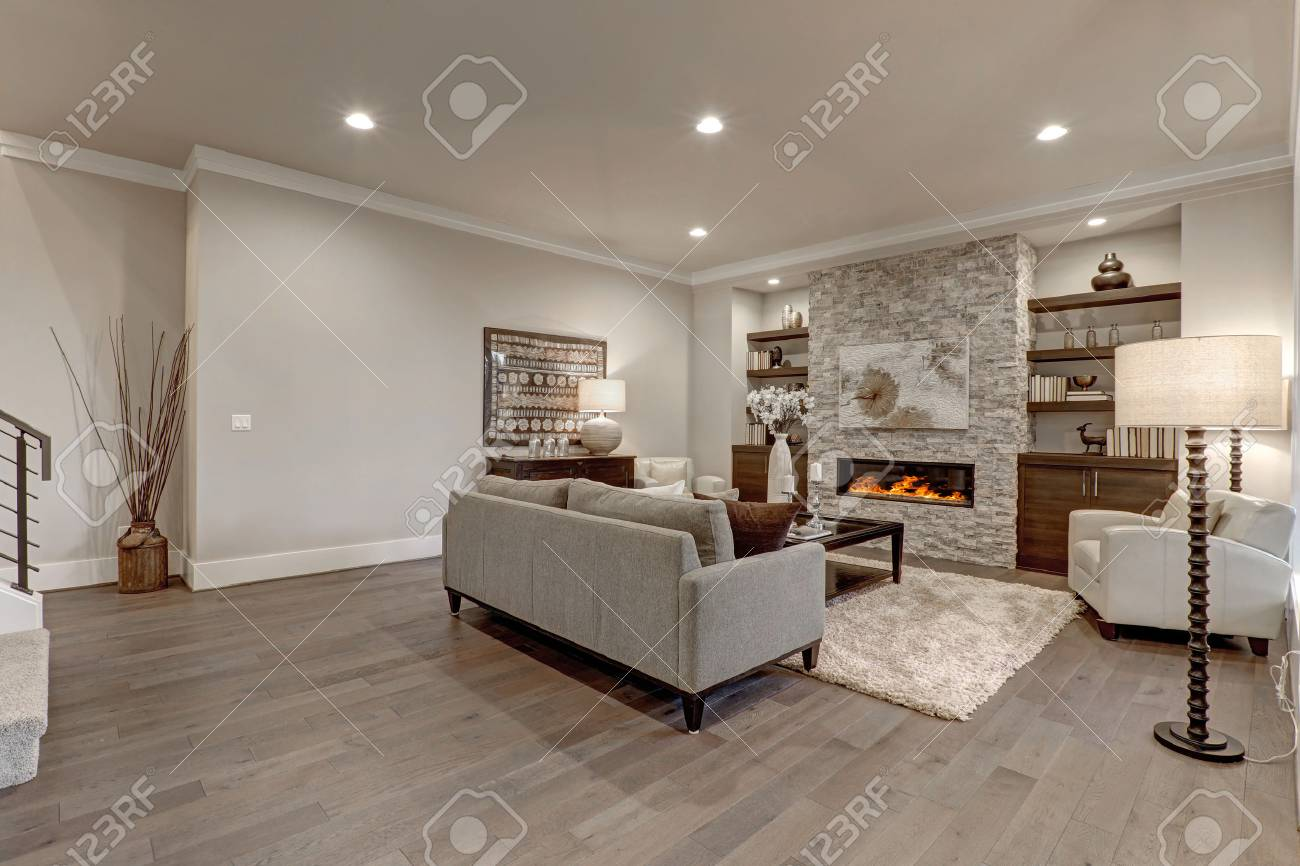 Living room interior in gray and brown colors features gray sofa atop dark hardwood floors facing stone fireplace with built-in shelves. Northwest, USA - 70106229