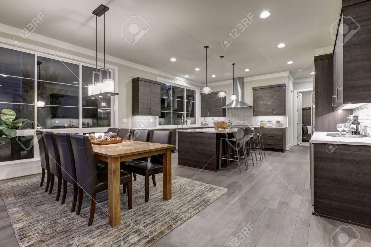 Casa de lujo de nueva construcción con plan de piso abierto: comedor y  cocina de diseño. Mesa de comedor de madera rústica coincide con sillas de  ...
