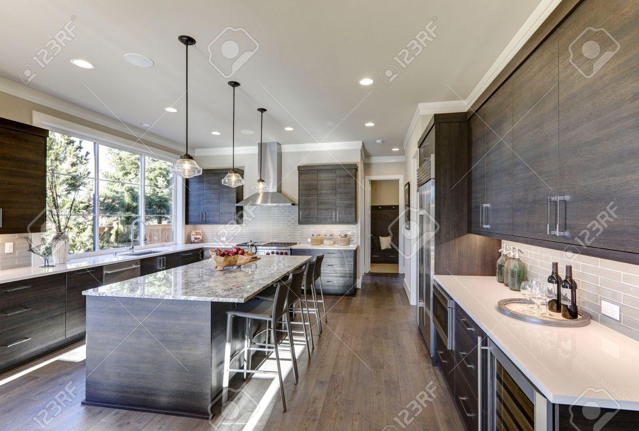 Moderne Graue Küche Verfügt über Dunkelgraue Flache Frontschränke Gepaart  Mit Weißem Quarz Arbeitsplatten Und Einer