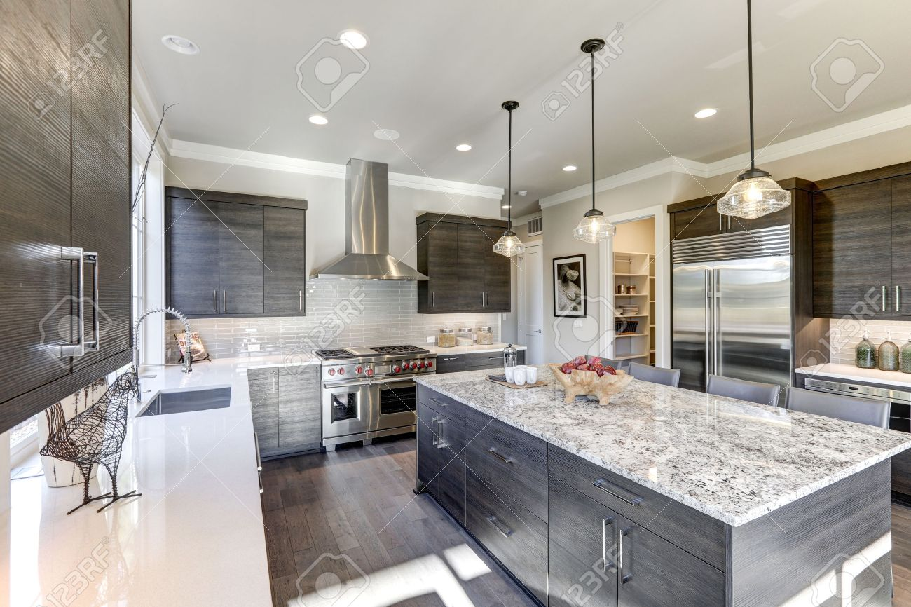 Modern gray kitchen features dark gray flat front cabinets paired with white quartz countertops and a glossy gray linear tile backsplash. Bar style kitchen island with granite counter. Northwest, USA - 70177674