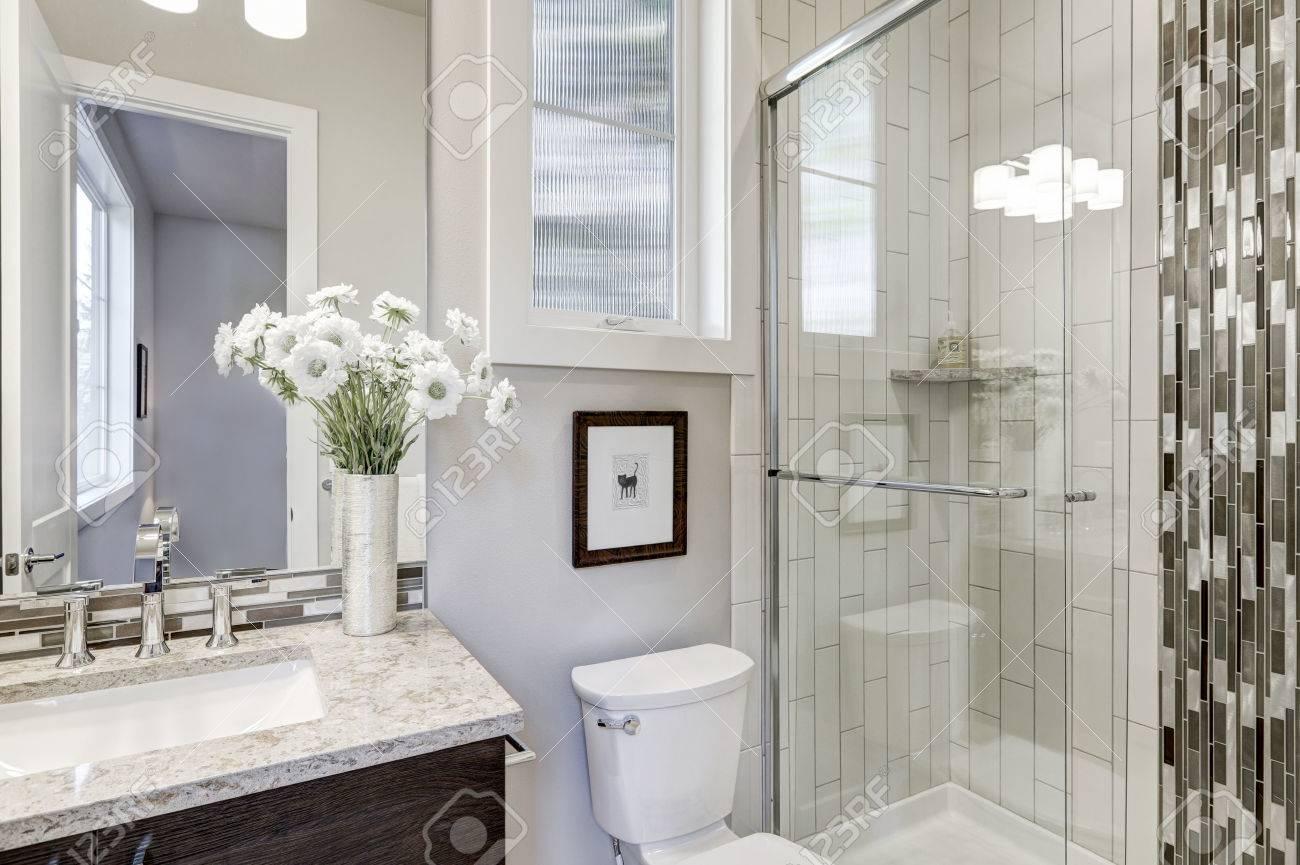 vidrio cabina de ducha con azulejos de metro blanco envolvente acentuado con la tira de baldosas
