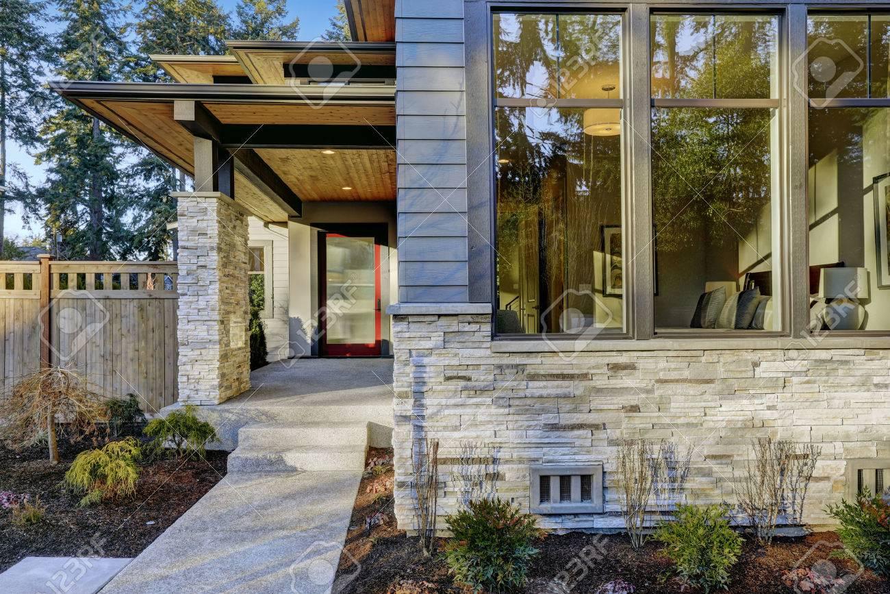 Entrée de la nouvelle maison de construction de luxe avec revêtement bleu  et une décoration en pierre. plomb allée en béton à porche couvert longue  ...