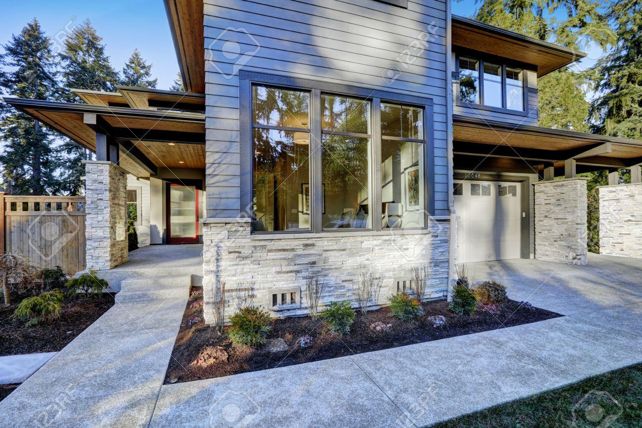 Décoration Entrée De Maison entrée de la nouvelle maison de construction de luxe avec revêtement bleu  et une décoration en pierre. plomb allée en béton à porche couvert longue