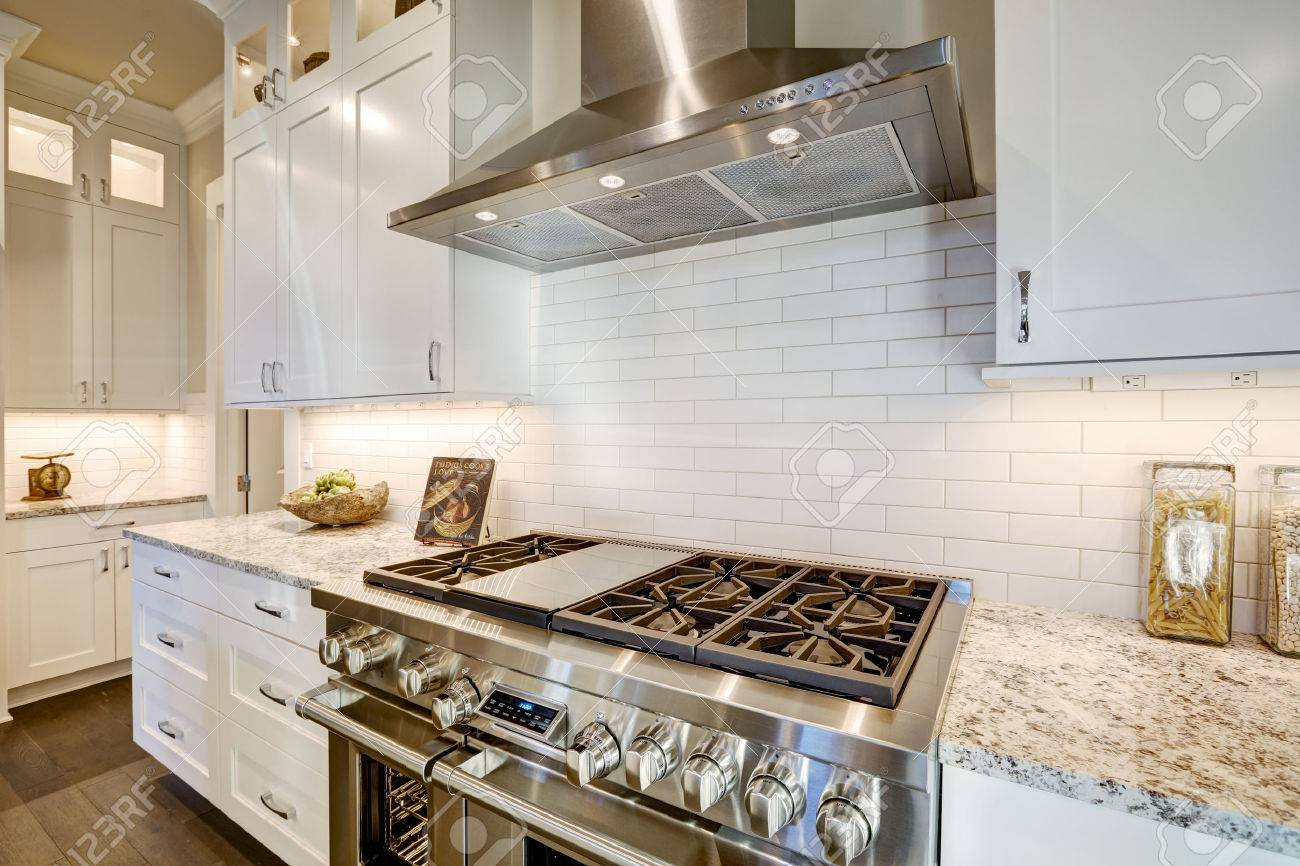 Beautiful kitchen features a nook filled with stainless steel stove hood white subway tile