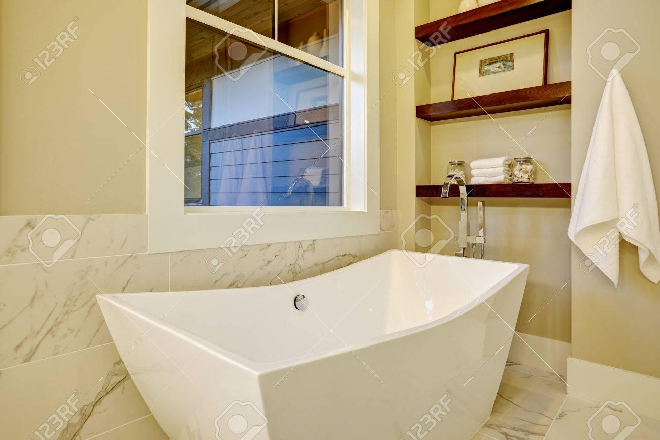 Coin salle de bain sophistiqué avec baignoire autoportante placée sous la  fenêtre, niche murale avec étagères et carrelage en marbre blanc et gris et  ...