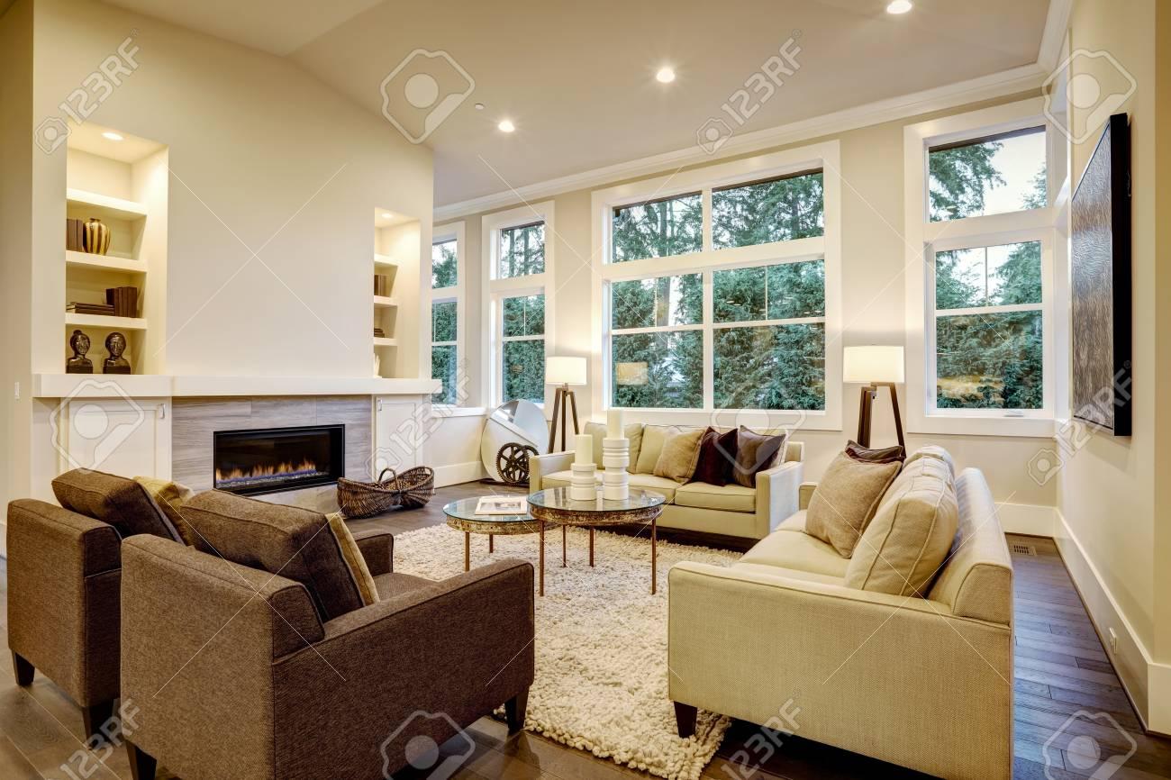 Design elegante soggiorno con pavimenti scuri. Arredato con piano in vetro  tavoli accento e divani beige condita con cuscini marroni fronte camino ...