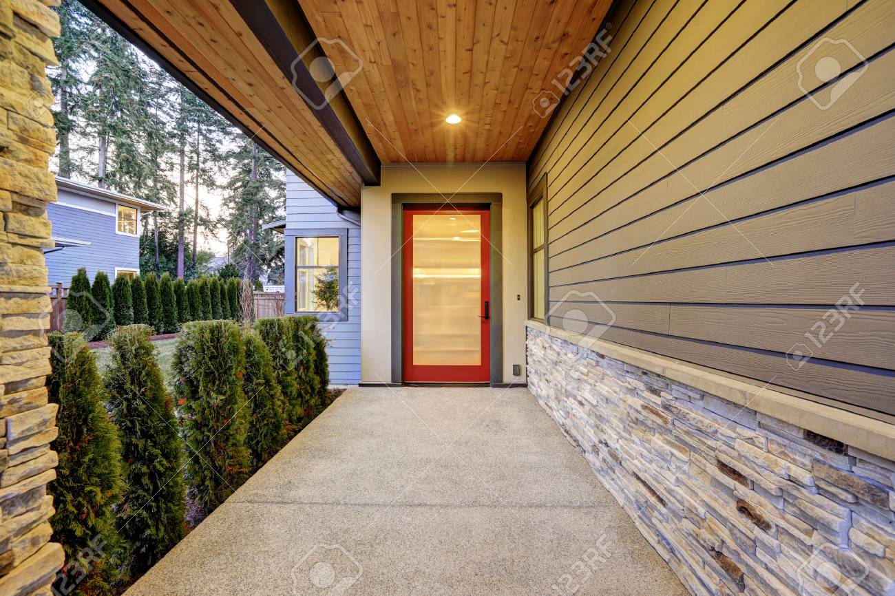 Entrance of Luxurious new construction home with long covered porch that features plank ceiling, natural stone wall design and modern glossy front door. Northwest, USA - 70296421