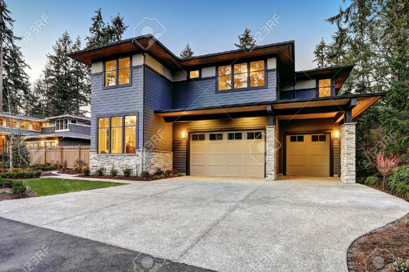 Luxurious new construction home in Bellevue, WA. Modern style home boasts two car garage framed by blue siding and natural stone wall trim. Northwest, USA - 70311787