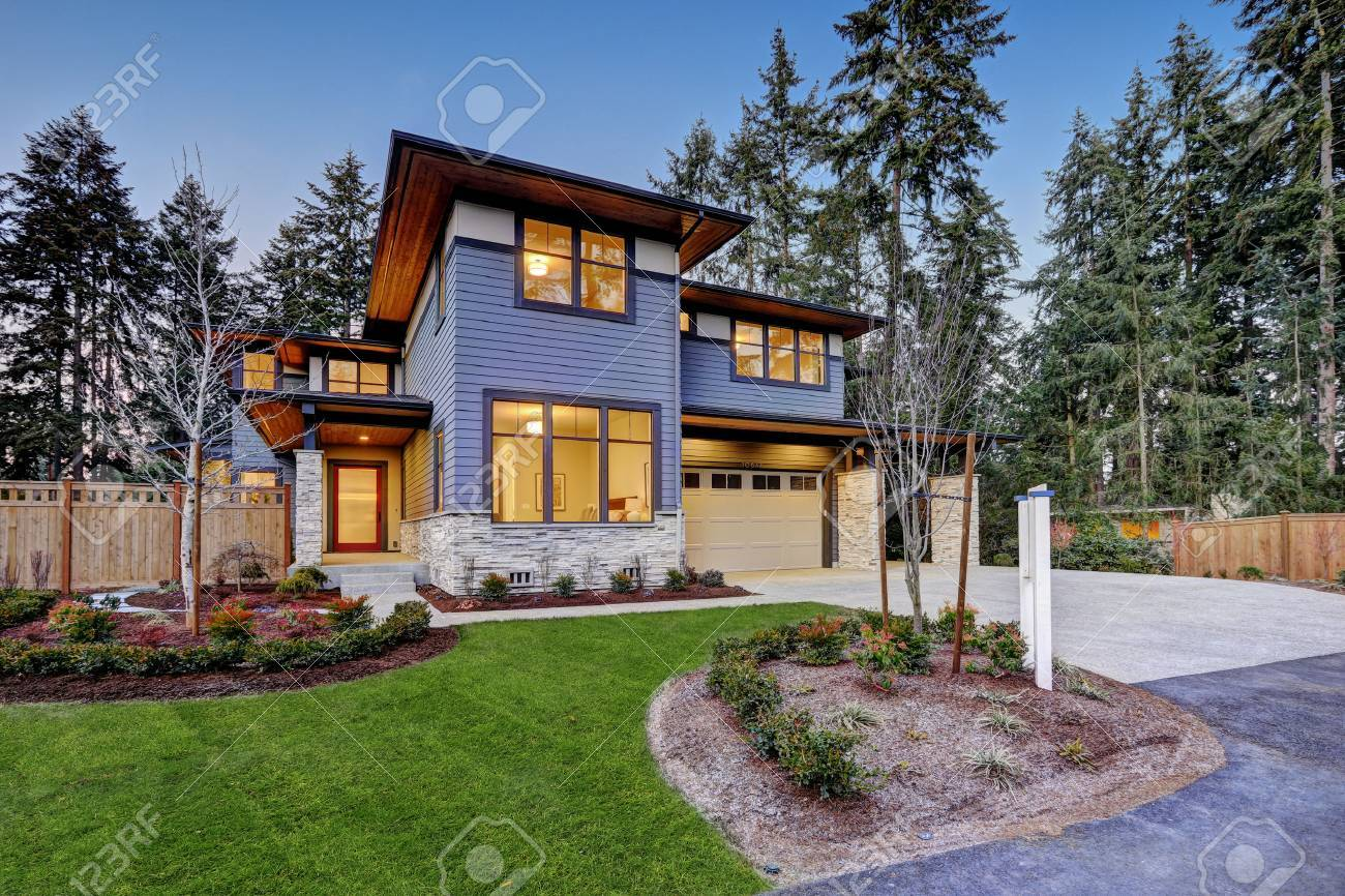 Luxurious new construction home in Bellevue, WA. Modern style home boasts two car garage framed by blue siding and natural stone wall trim. Northwest, USA - 70296417