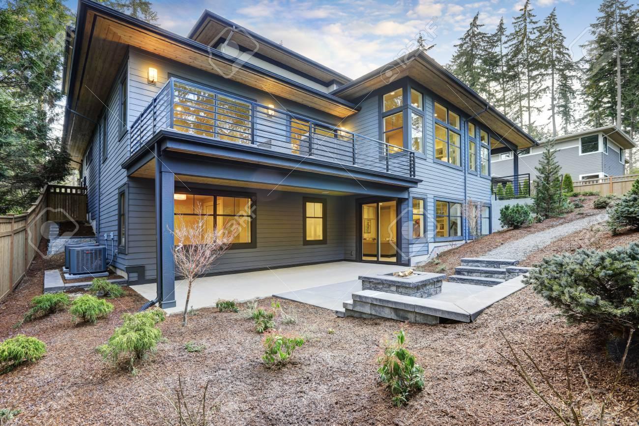 Casa De Lujo De Nueva Construcción Con El Revestimiento De Madera De Color Azul Patio Con Pozo De Fuego En El Primer Piso Y La Terraza Con Muebles De