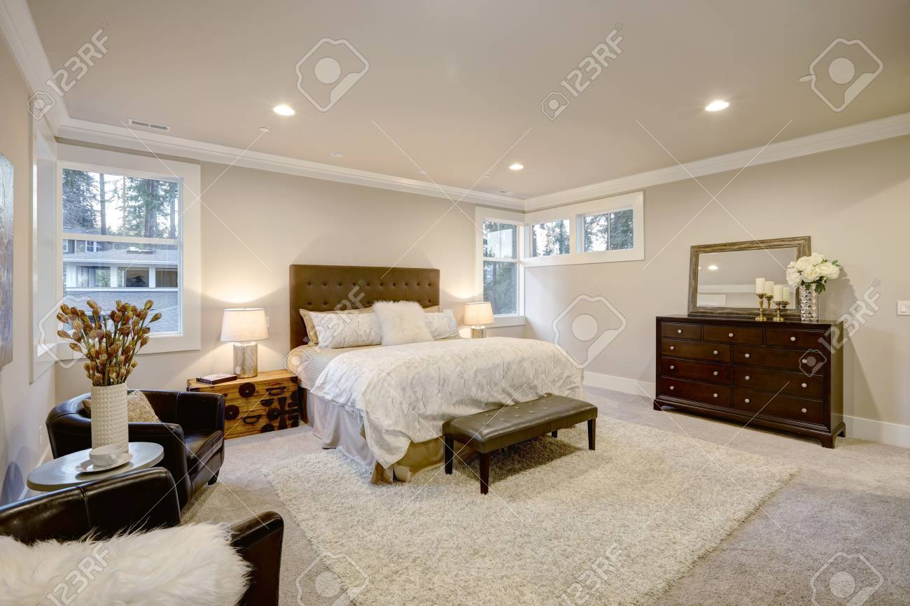 Beige And Brown Master Bedroom Boasts Queen Bed With Taupe Tufted Stock Photo Picture And Royalty Free Image Image 70296410