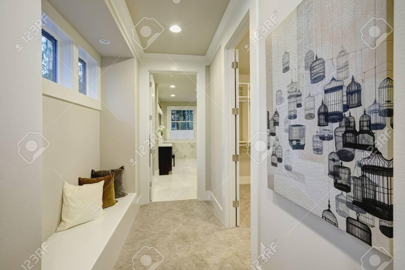 L\'espace blanc de couloir avec siège intégré en tête avec des oreillers  gris et blanc et brun en dessous de petites fenêtres. Northwest, États-Unis