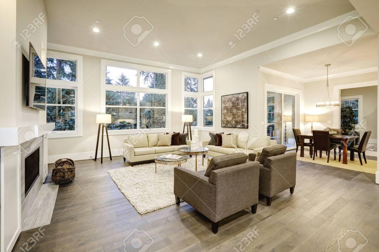 Chic salon design avec planchers sombres. Meublé avec plateau en verre  tables d\'appoint et des canapés beige surmonté d\'oreillers marron.  Northwest, ...