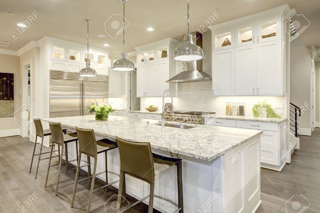 Caractéristiques Design White grande cuisine îlot de cuisine de style bar  avec comptoir de granit éclairé par les lumières pendants modernes. ...