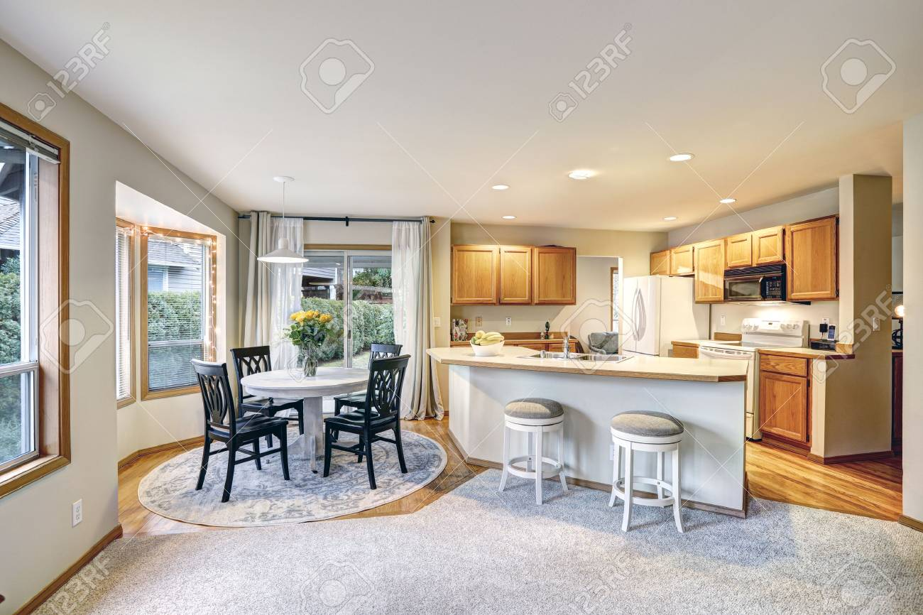 Traditional dining and kitchen room design. Kitchen has white..