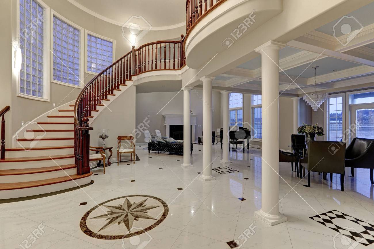 Stunning spacious entry foyer with columns boasts marble mosaic stunning spacious entry foyer with columns boasts marble mosaic tile floor and grand staircase with glossy dailygadgetfo Gallery