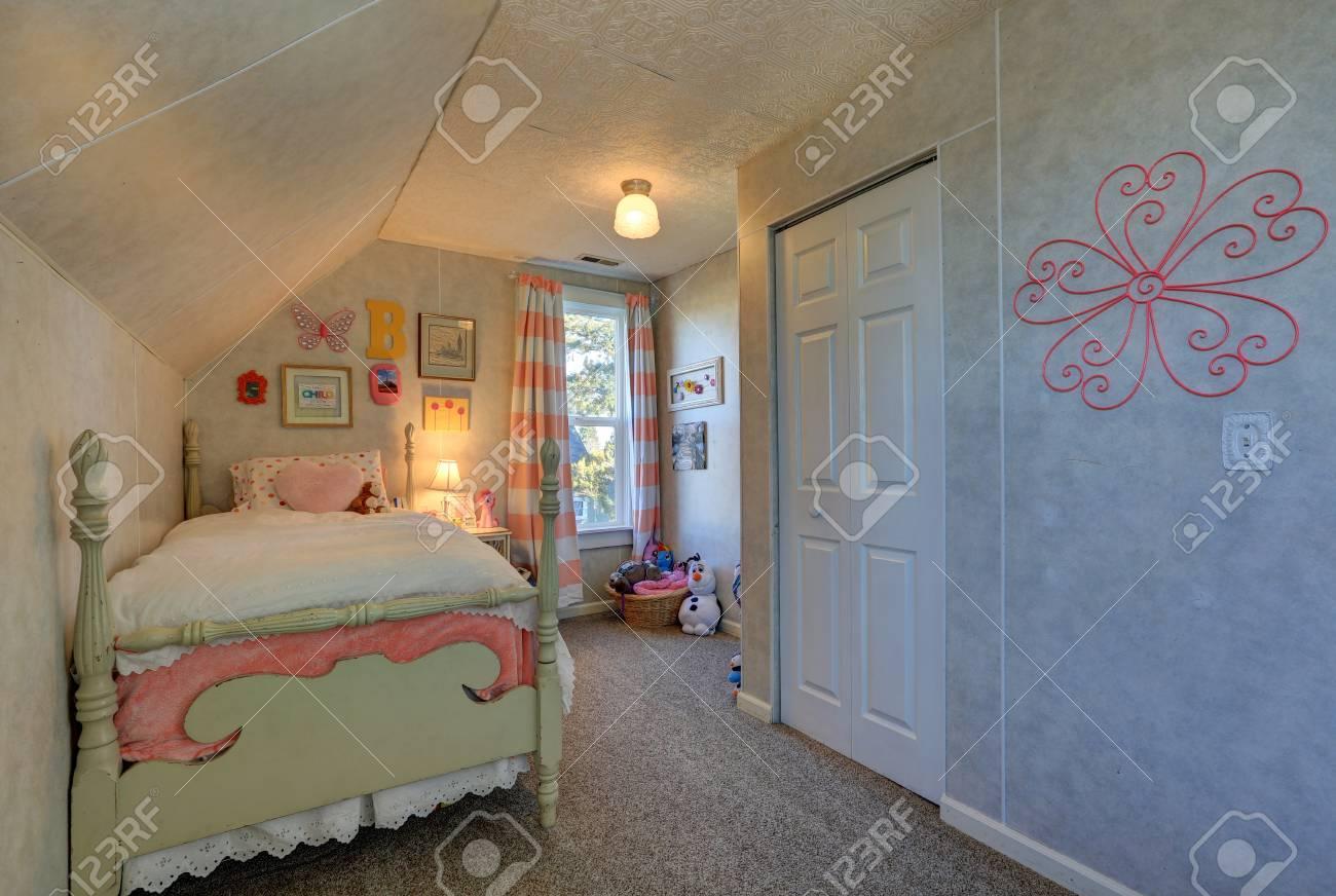 Papier Peint Chambre Mansardée chambre mansardée pour fille rose et verte avec plafond en pente au dessus  du lit à baldaquin et petite fenêtre habillée de rideaux à rayures roses.