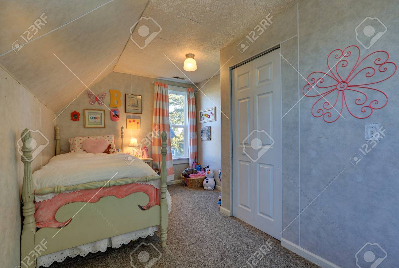 Pink and green girl\'s attic bedroom with sloped ceiling over..