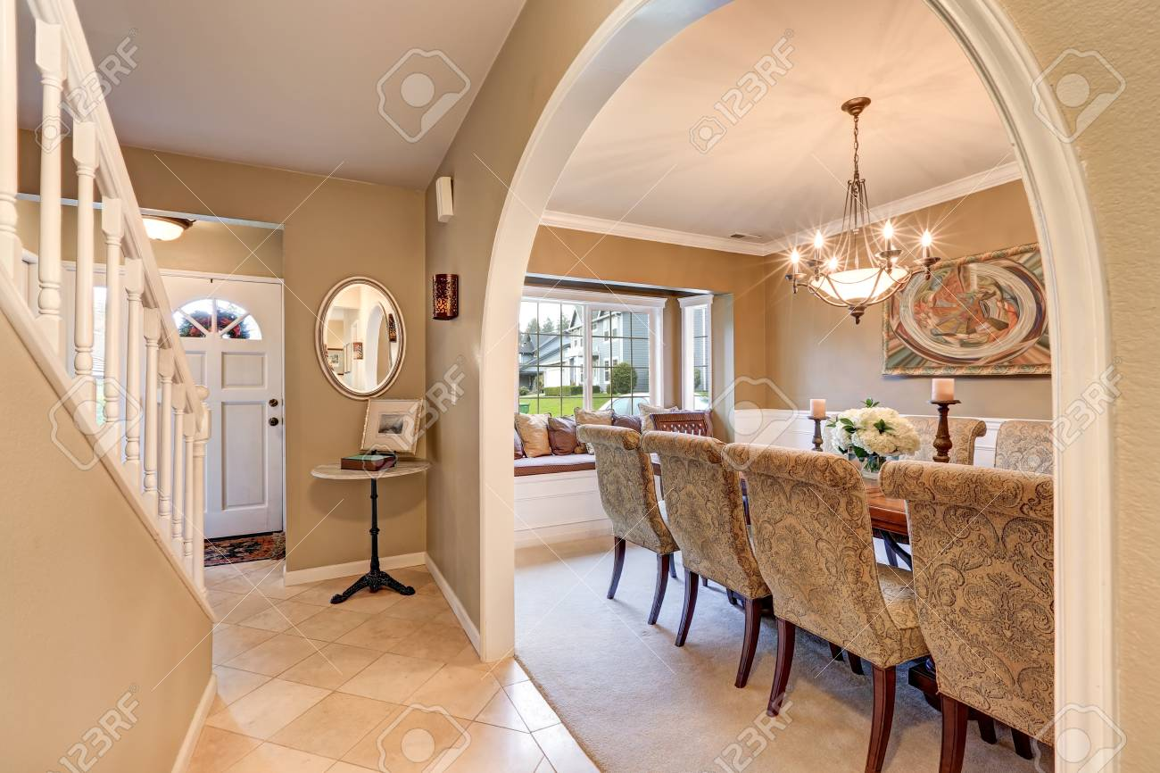 Arched Entryway To Elegant Formal Dining Room With Tan Walls