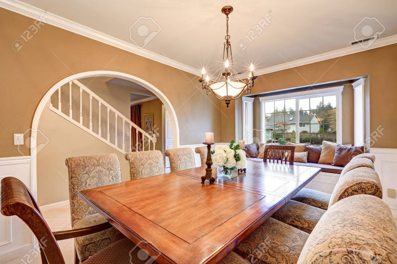 Elegant Interior Design Of Formal Dining Room With Tan Walls Wainscoting Arched Doorway