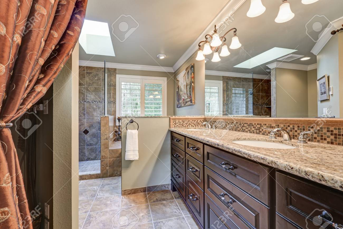 Freshly remodeled bathroom with gorgeous dual sink vanity accented with dark cabinets, granite counters and mosaic backsplash, and skylight over jetted tub and walk-in shower. Northwest, USA - 71769648