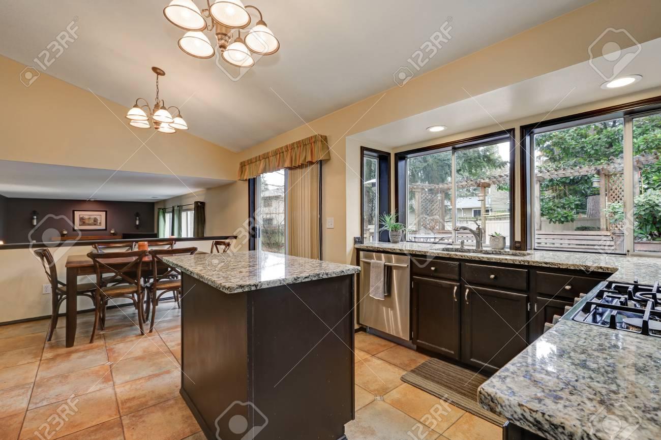 Design classico pranzo Cucina con isola Cucina, armadi in legno scuro  sormontato da granito lucidi, elettrodomestici in acciaio inox e pavimento  di ...